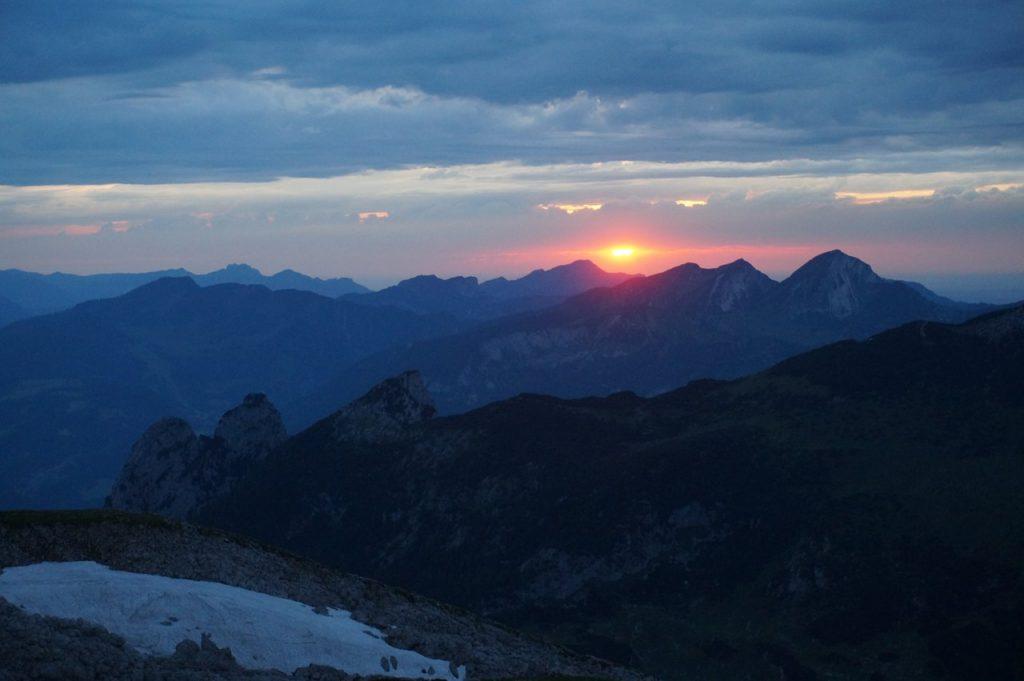 Dunkelrot leuchtet die Sonne bevor sie hinter den Bergen verschwindet