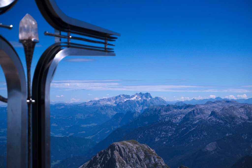 Der Kristall des Gipfelkreuzes und dahinter das Dachsteinmassiv mit dem Hallstätter Gletscher