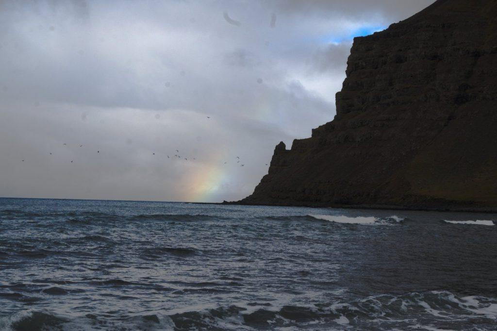 Regenbogen an der Küste bei Skálavík